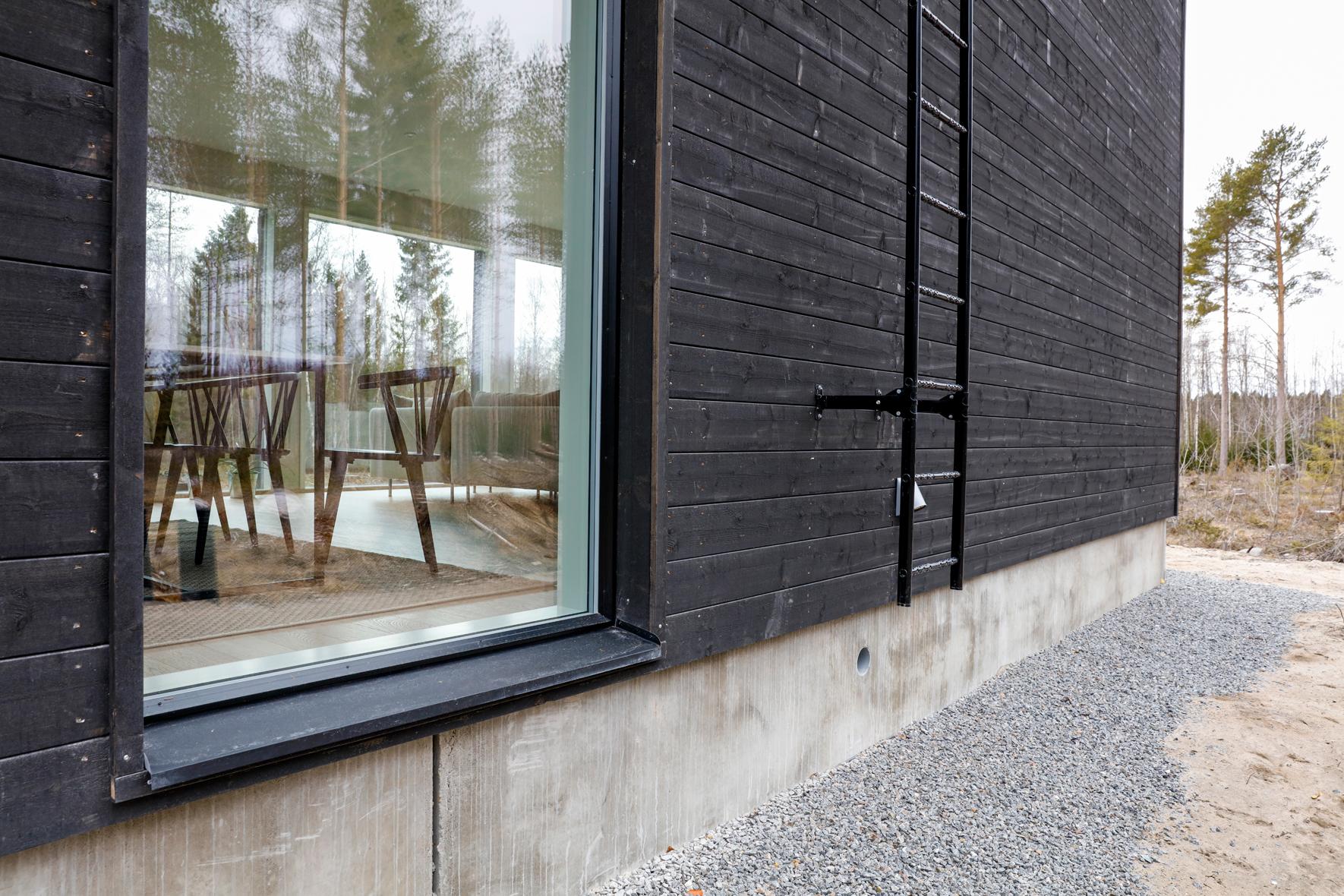 Svart panelad utsida med stora fönster