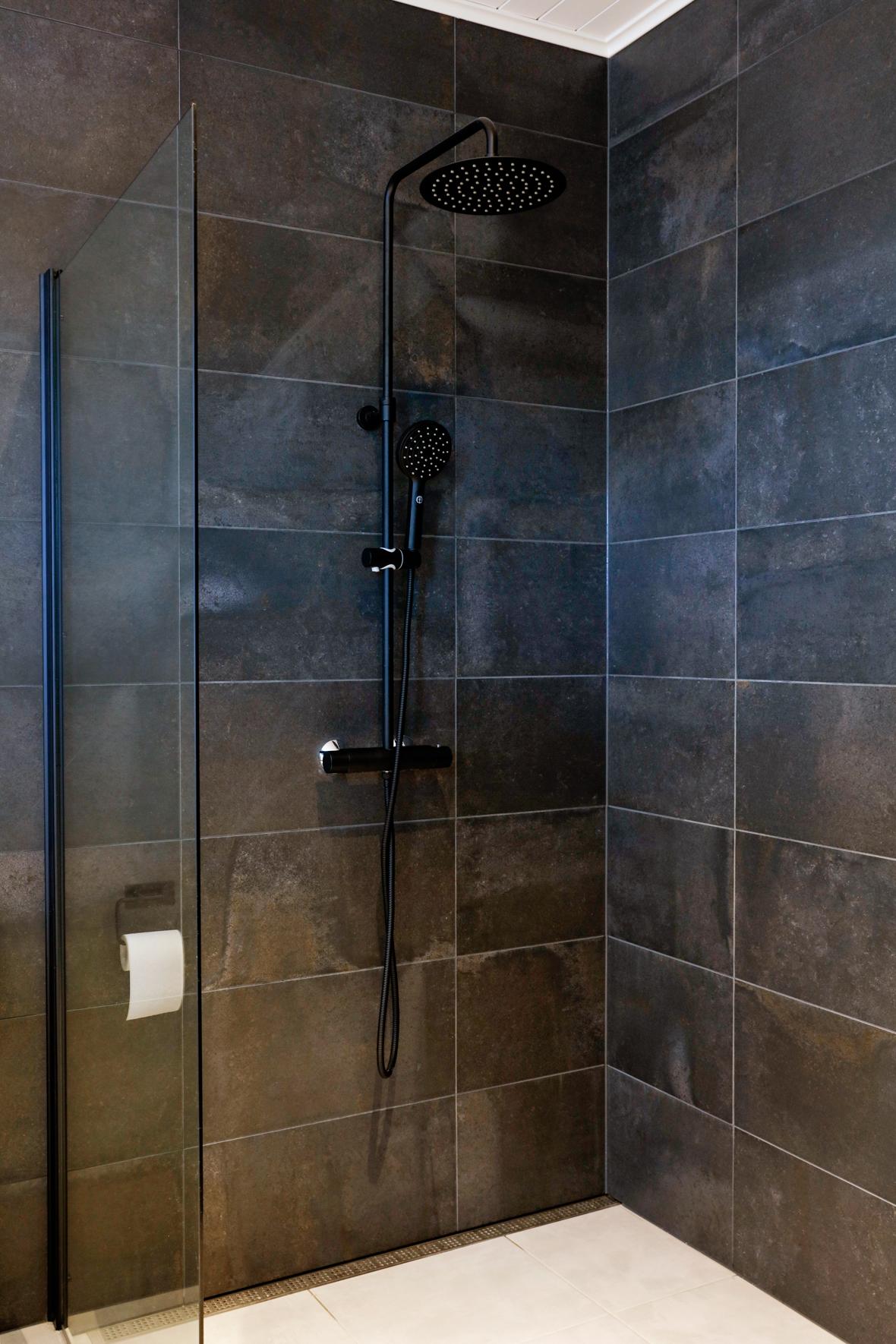 En unidrain golvsil i badrum med stora, mörka kakel.