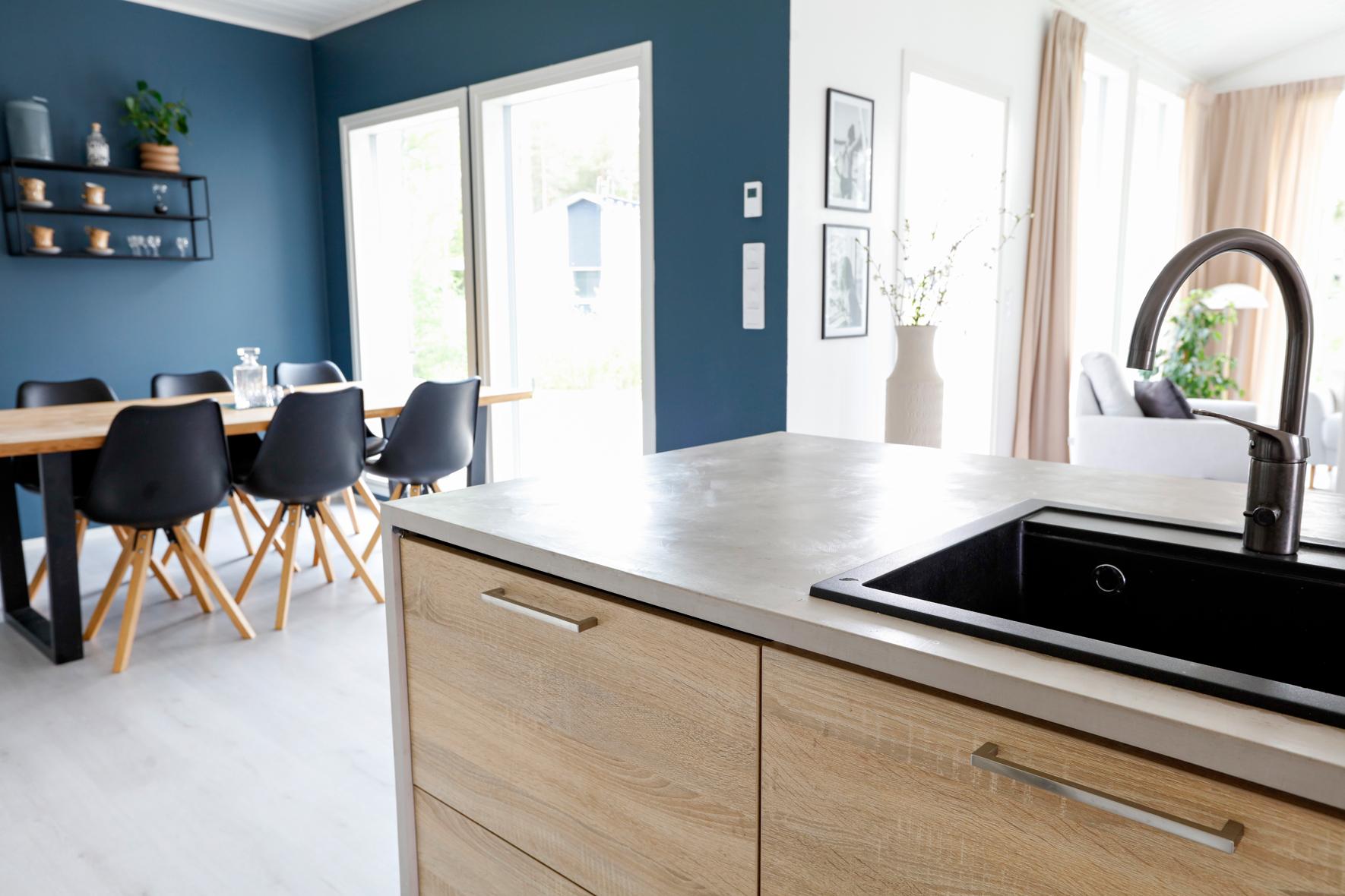 En betongköksö i blått kök med trälädor