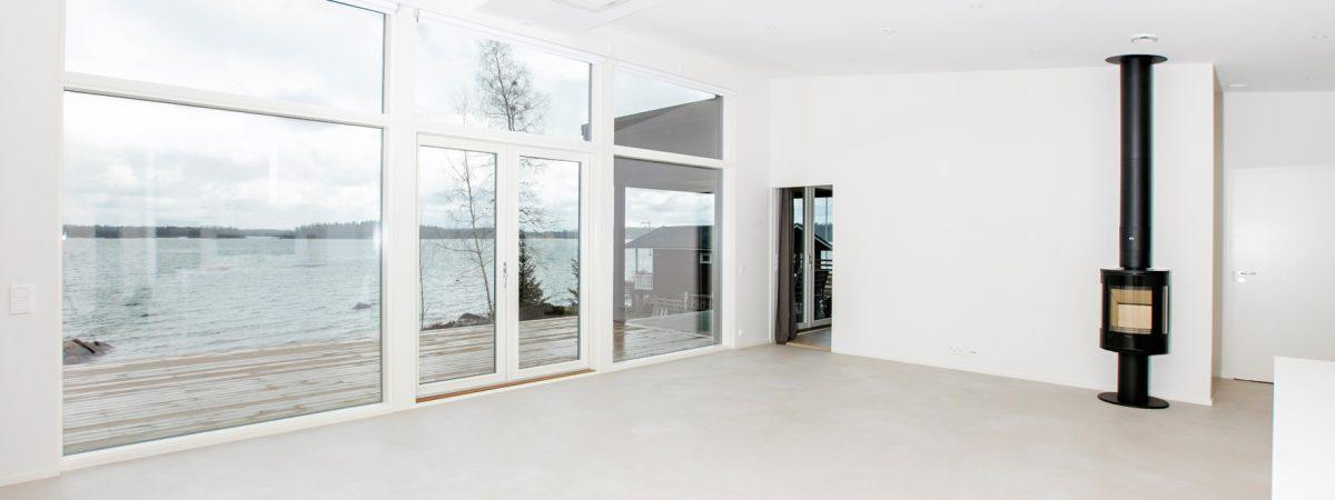 Utsikt mot sjö från vardagsrum med stora fönster och spis